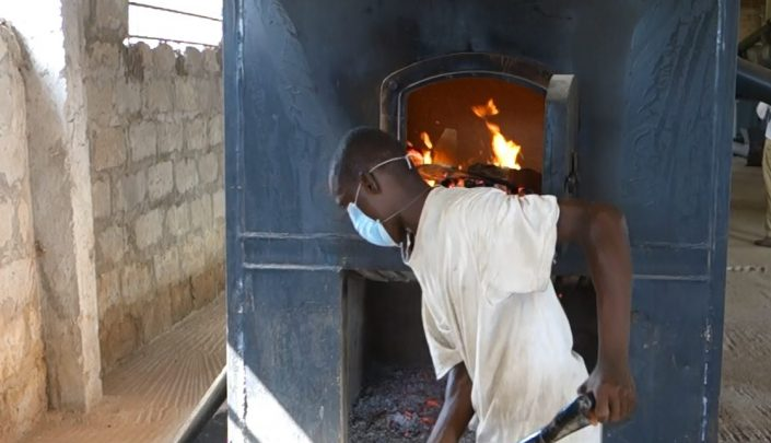 Employee feeding raw material into the furnace to generate heat for the dryer